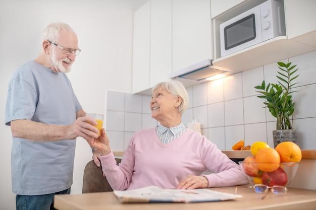 Fürsorglicher ehemann. älterer grauhaariger mann, der seiner frau ein glas orangensaft gibt