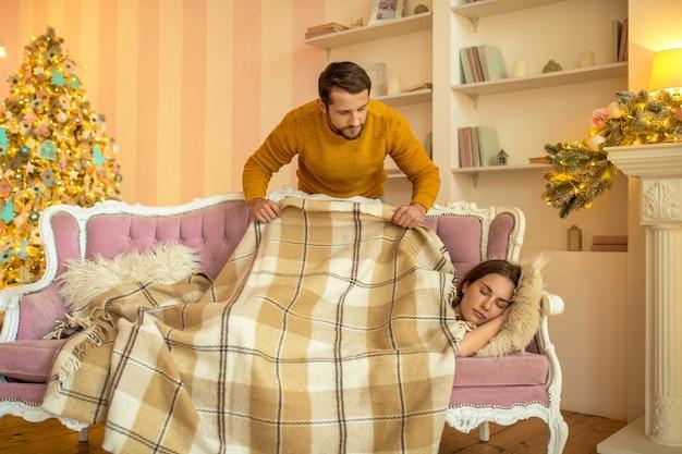 Fürsorglicher ehemann, der seine schlafende frau mit einem plaid bedeckt