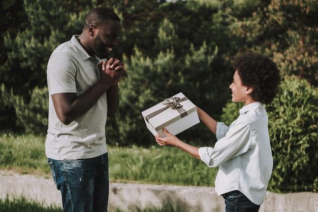 Fürsorglicher junge gibt geschenk und schaut vater an