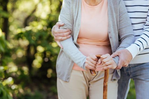 Fürsorglicher, liebevoller älterer mann, der sich um seine alte frau kümmert und ihr hilft, schritte zu machen, während er die frau umarmt und im park spazieren geht