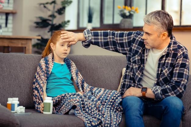 Fürsorglicher papa. netter angenehmer mann, der die stirn seiner tochter berührt, während er ihre temperatur überprüft checking