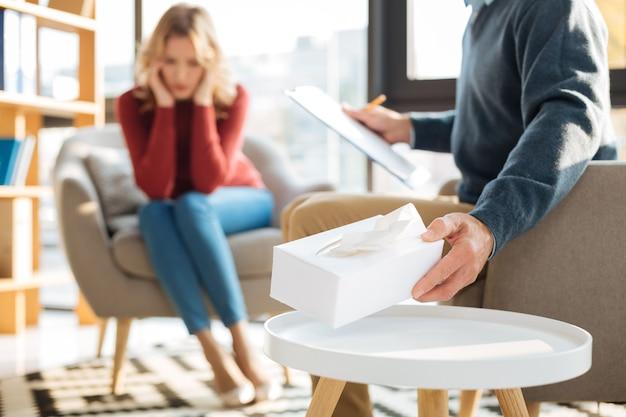 Fürsorglicher psychologe. selektiver fokus einer schachtel mit papiertaschentüchern, die von einem intelligenten männlichen psychologen genommen werden