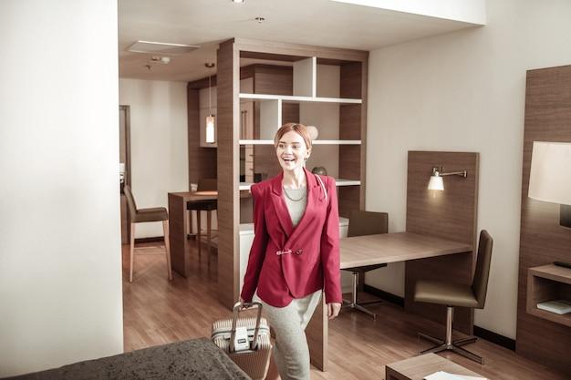 Fürsorgliches gepäck. blonde geschäftsfrau, die ihr gepäck trägt, während sie hotelzimmer betritt