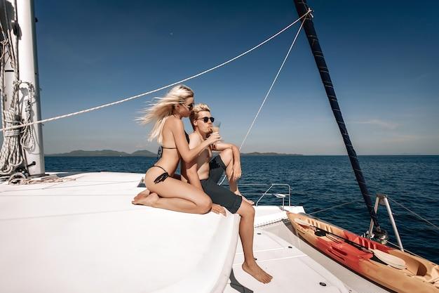 Fürsorgliches paar, das auf ihrer riesigen weißen yacht aufwirft. schönes mädchen, das ein kaltes getränk in der hand hält und ihrem freund einen vorgeschmack darauf gibt.