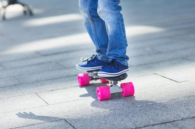 Füße auf einem skateboard. kinderfüße auf der straße im freien. junge, der einen schlittschuh trägt, der turnschuhe nah oben trägt