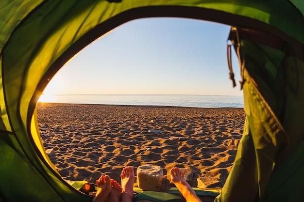 Füße aus einem zelt mit blick auf die küste