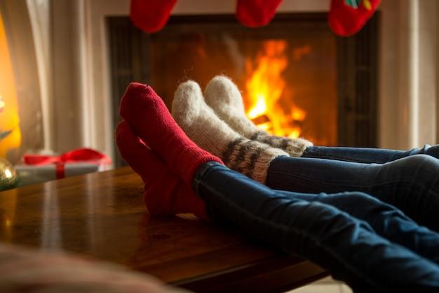Füße der familie in wollsocken, die sich in der nähe eines brennenden kamins im wohnzimmer erwärmen