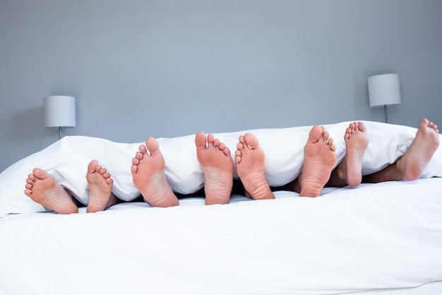 Füße der familie ragen aus der decke
