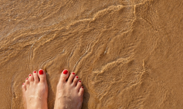 Füße der frau am sommerstrand