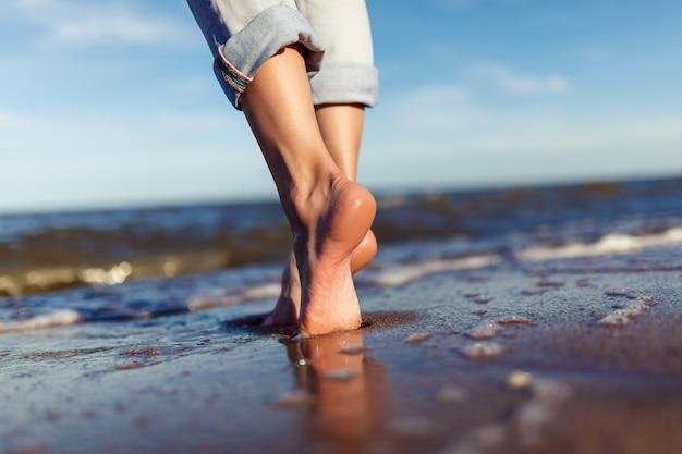 Füße der frau in den meereswellen