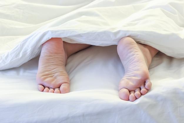 Füße der schlafenden frau im weißen schlafzimmer