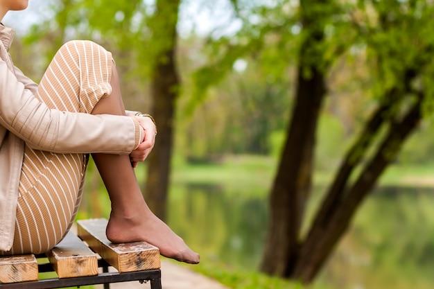 Füße der schönen jungen frau, die auf bank im park sitzt.