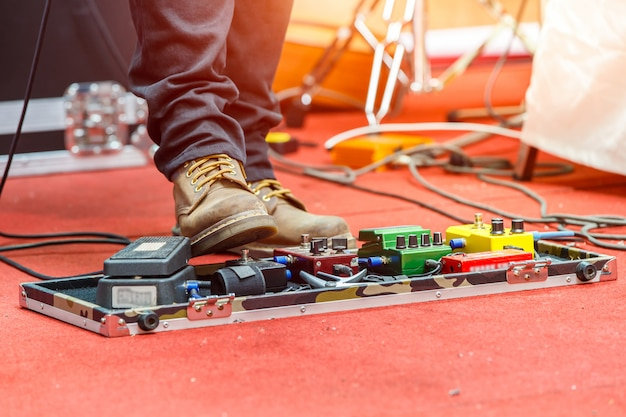 Füße des gitarristen auf einer bühne mit verzerrungseffektpedalen. tiefenschärfe