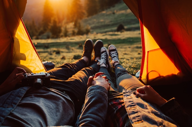 Füße des jungen paares, das im zelt für das wandern auf berg während des sonnenuntergangs liegt.