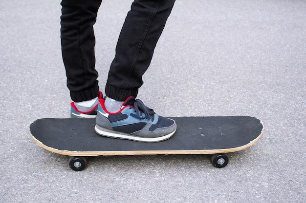 Füße des kindes in turnschuhen, schwarzen hosen und skateboard auf dem bürgersteig
