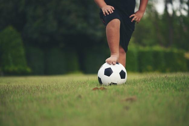 Füße des kleinen jungen, die fußball an der rasenfläche halten