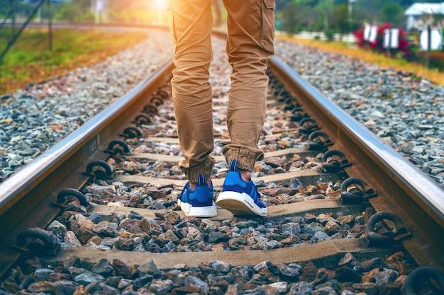 Füße des mannes, der auf eisenbahn geht. reisekonzept.