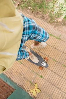 Füße des mannes stehen auf longboard