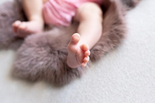 Füße des neugeborenen. pinke farbe. muttertag. neugeborenes mädchen