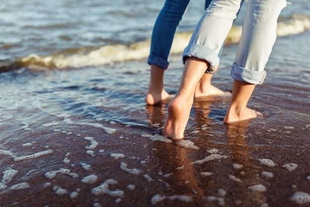 Füße des paares frau und mann in den meereswellen