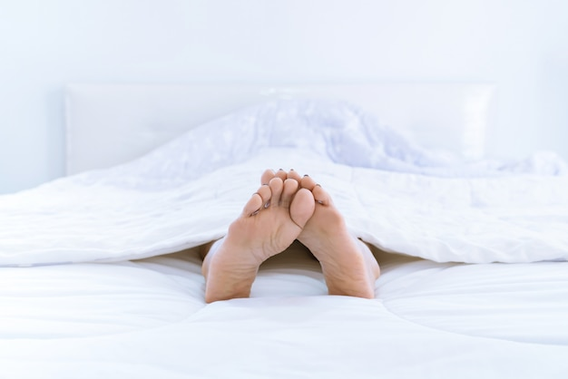 Füße einer frau, die zu hause im bett schläft. - beine einer frau liegen auf weißem bett.