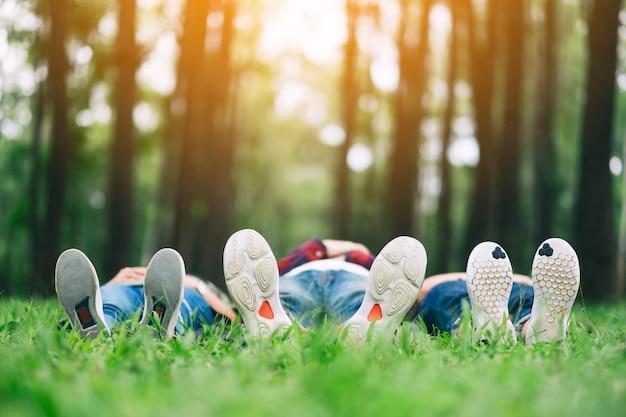 Füße einer gruppe junger leute beim liegen auf einem grünen gras im wald