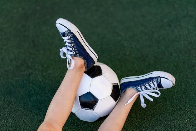 Füße eines jungen mit einem fußball auf einem grünen rasen auf einem fußballfeld