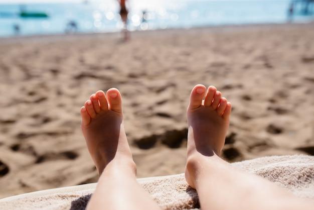Füße eines kindes am strand.
