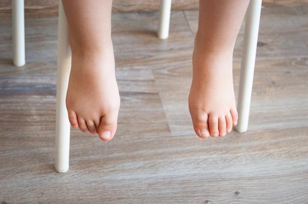 Füße eines kindes, das in einem stuhl sitzt. natürliche beleuchtung
