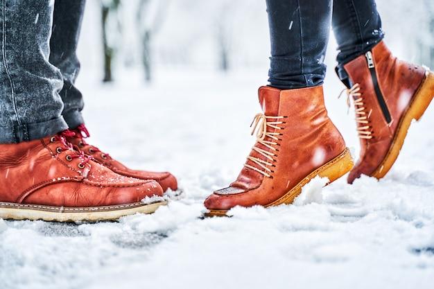Füße eines paares auf einem schneebedeckten bürgersteig in den braunen stiefeln