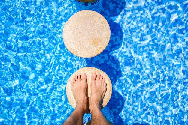Füße eines urlaubers, der sich in einem pool entspannt