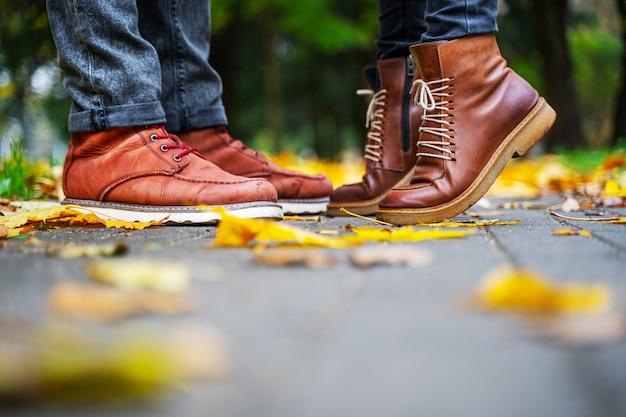 Füße eines verliebten paares in den braunen schuhen auf dem weg des herbstparks, gestreut mit gefallenen blättern. mädchen steht auf den zehen. kuss-konzept