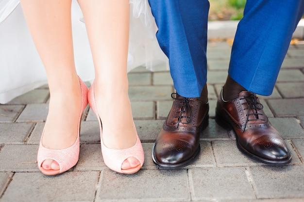 Füße in den hochzeitsschuhen von braut und bräutigam