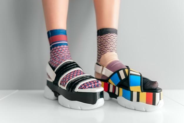 Füße in nicht passenden trendigen socken, die in zwei verschiedenen modischen sandalen aus hochkeilem leder stehen