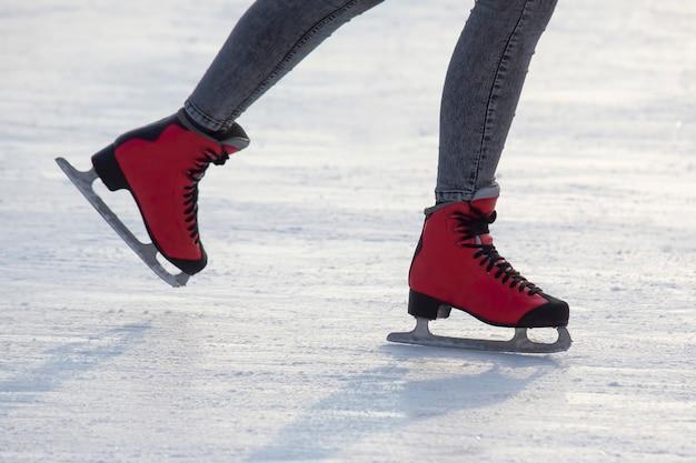 Füße in roten schlittschuhen auf einer eisbahn. hobbys und freizeit. wintersport