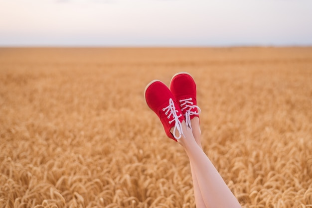 Füße in roten schuhen lustig aus weizenfeld herausragen. sei du selbst.