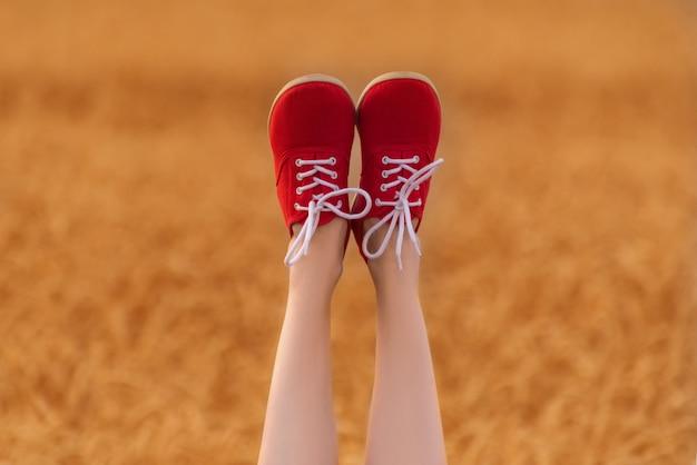 Füße in roten schuhen nach oben. schlanke weibliche beine auf weizenfeld.