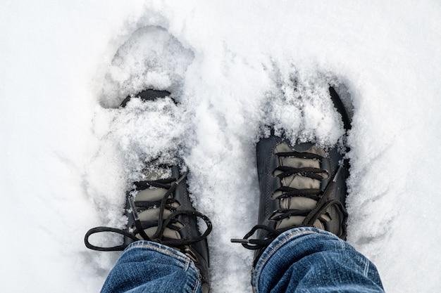 Füße in schwarzen trekkingstiefeln auf schnee