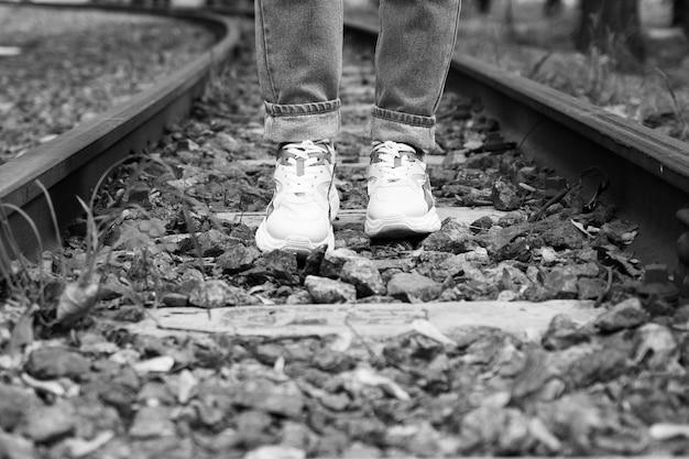 Füße in turnschuhen auf den eisenbahnschienen
