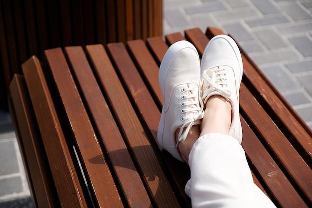 Füße mädchen in weißen schuhen auf einer bank im park. nahansicht.