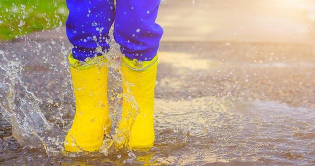 Füße mit gummistiefeln hüpfen in einer pfütze
