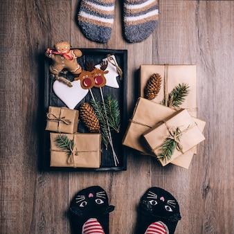 Füße mit warmen wintersocken und katzenpantoffeln stehen vor weihnachtsgeschenken.