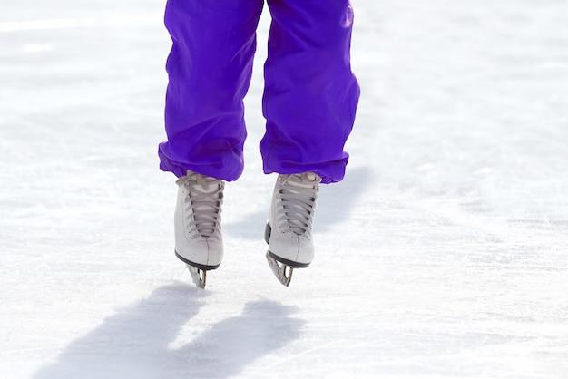 Füße schlittschuhlaufen auf der eisbahn. sport und unterhaltung. ruhe und winterferien.