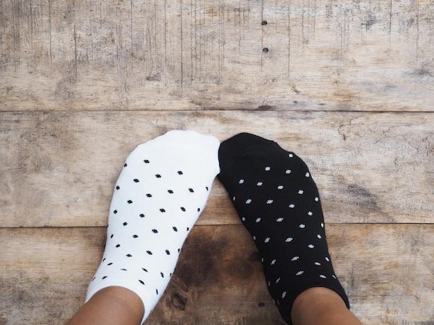 Füße tragen schwarze und weiße tupfensocken