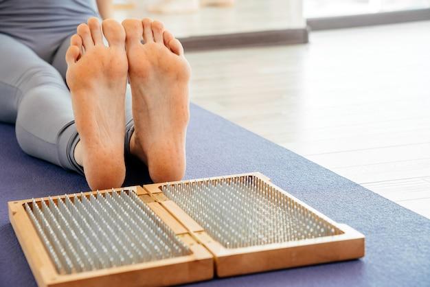 Füße und holzbrett mit scharfen metallnägeln. sadhu trittbrett. yoga entspannungstraining