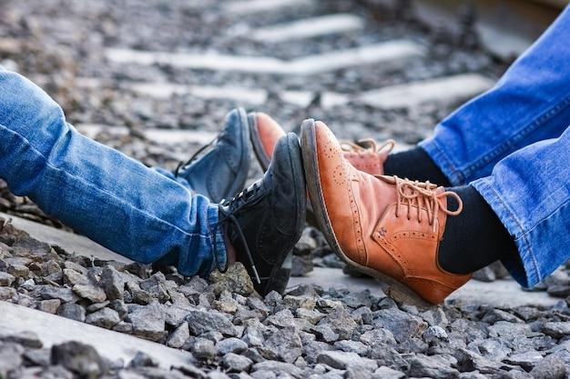 Füße vater und sohn cowboy schuhe in der nähe von eisenbahn