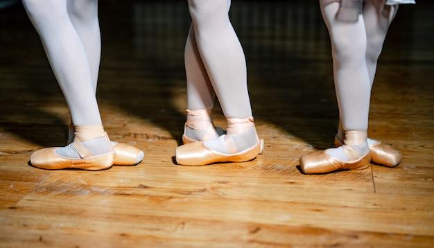 Füße von drei jungen ballerinas in spitzenschuhen