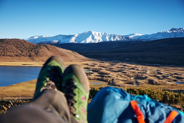 Füße wanderer entspannend genießen aussichtseingang im freien. travel lifestyle konzept abenteuerurlaub im freien.