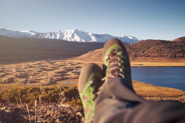 Füße wanderer entspannend genießen blick eingang im freien. reisen lifestyle konzept abenteuerurlaub im freien.