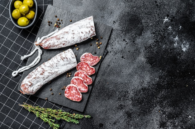 Fuet salami in scheiben geschnitten und rosmarin. traditionelle spanische wurst. draufsicht